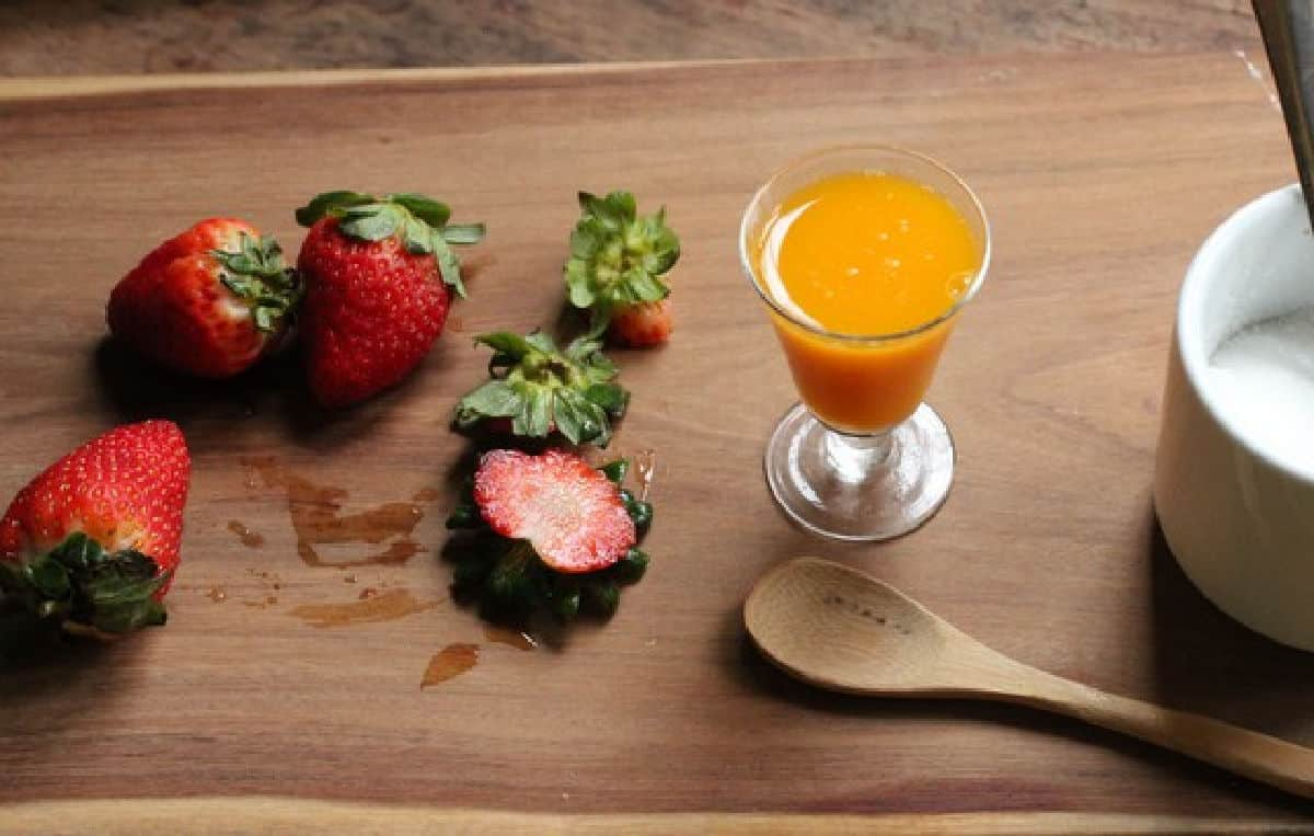 Wooden board with strawberries with small glass with juice