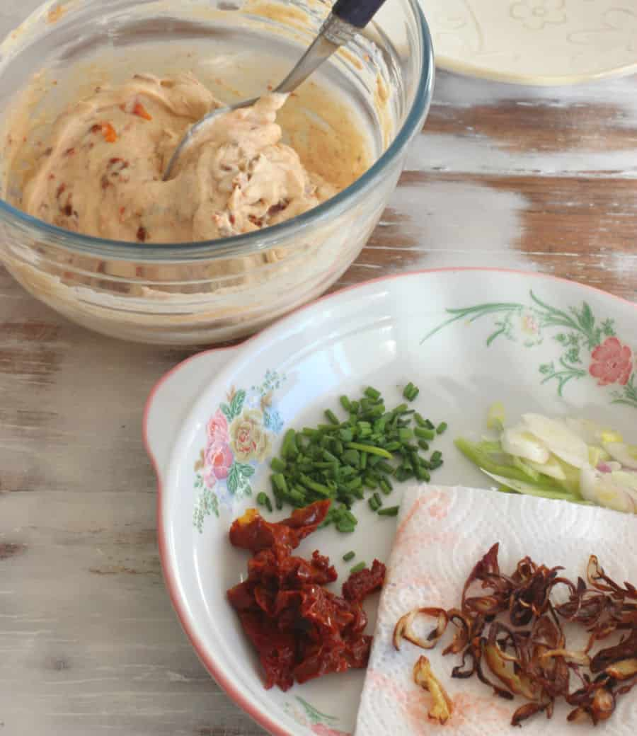 Glass bowl with creamy mixture, a shallow plate with chopped ingredients