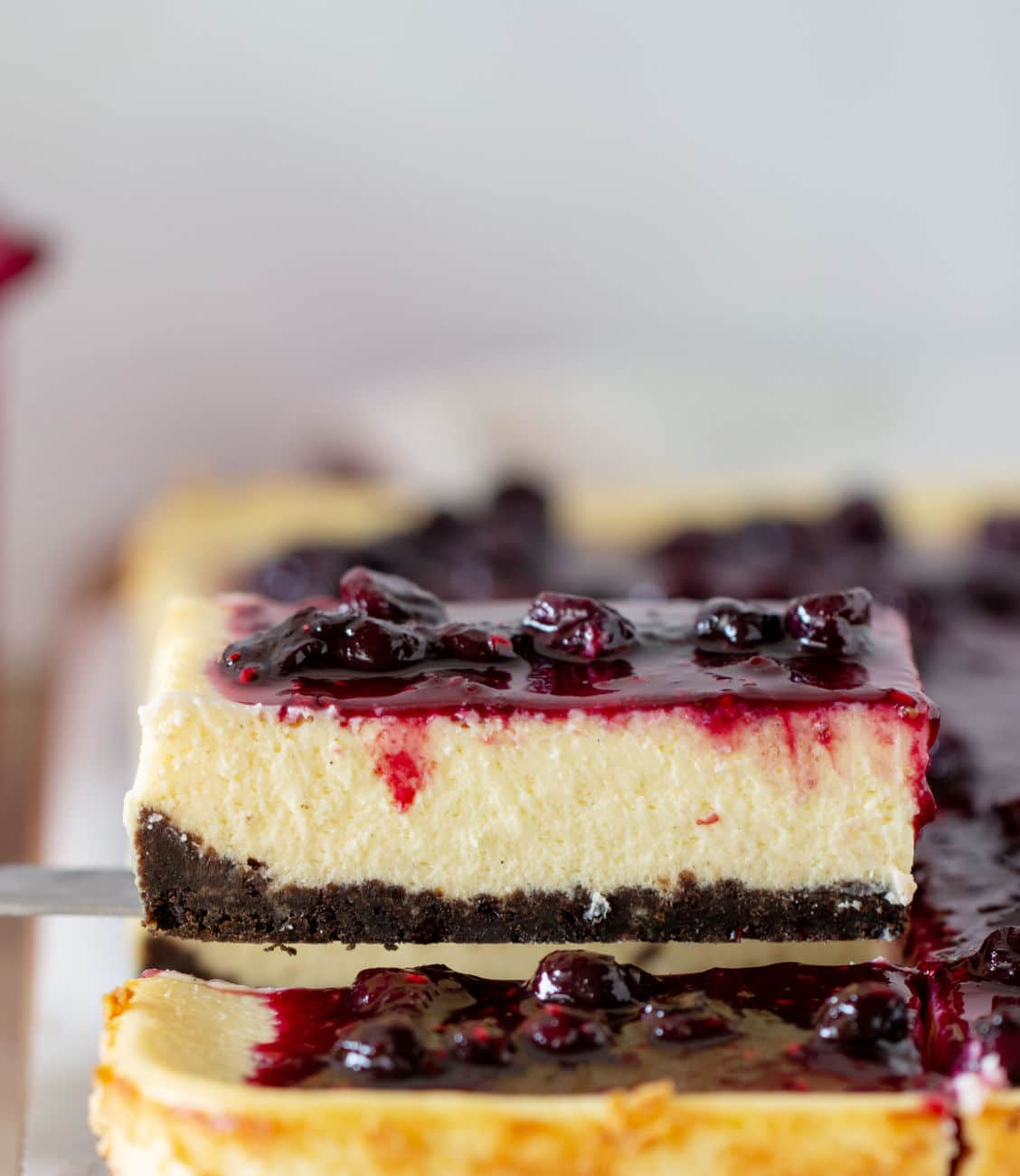 Slice of berry topped cheesecake being lifted from whole cake