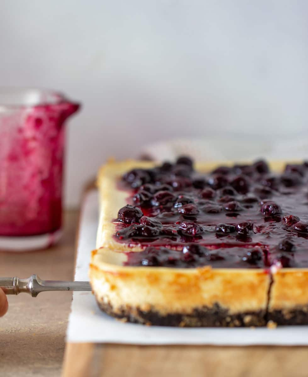 Berry topped cheesecake on wooden board, sauce jar