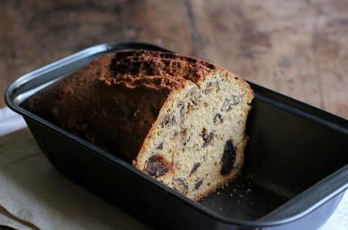 Half date loaf in metal pan on wooden table