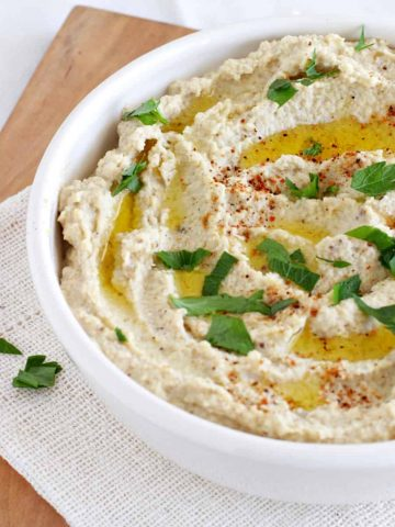 White bowl with eggplant hummus on wooden board. Parsley and olive oil garnish.
