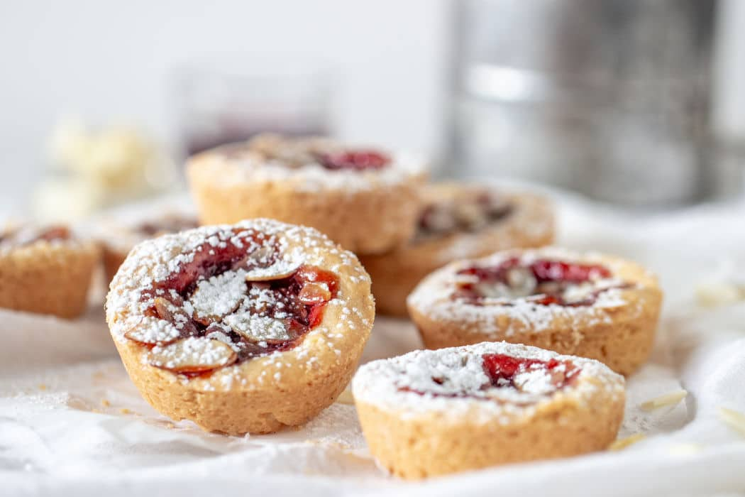 Several jam cakes sprinkled with powdered sugar, white surface, props in background