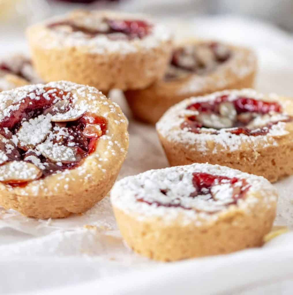 Several mini jam cakes on white cloth, sprinkled with powdered sugar