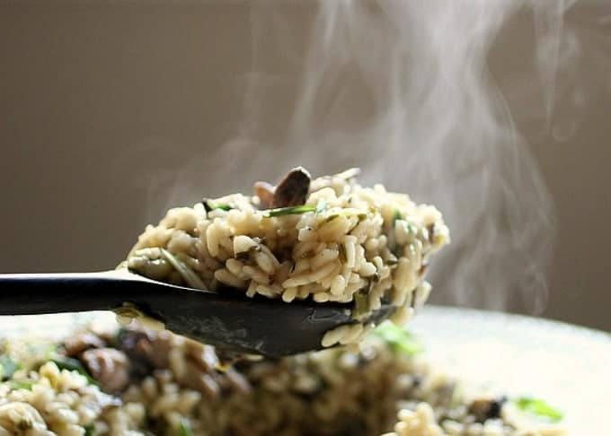 Steaming serving spoon full of risotto