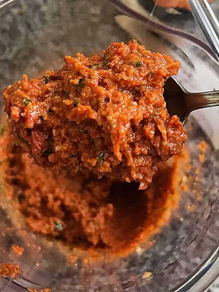 Spoon with sun dried tomato pesto over glass jar