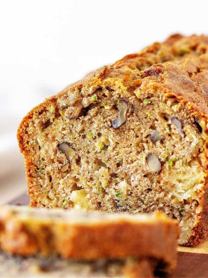 Cut loaf of zucchini bread with slices, white background