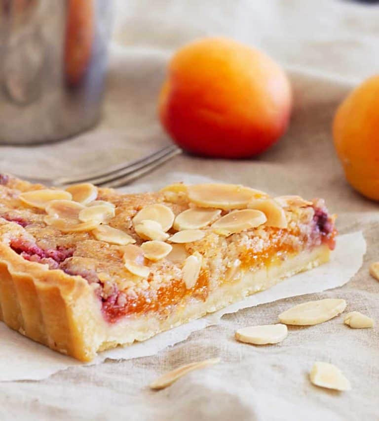 Slice of apricot tart on beige cloth, whole apricots, loose almonds