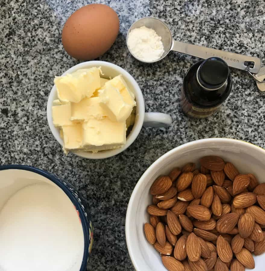 Frangipane ingredients on grey counter. Bowl with almonds, sugar, butter. One egg.
