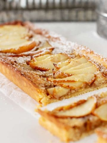 Cut rectangular pear tart on white surface