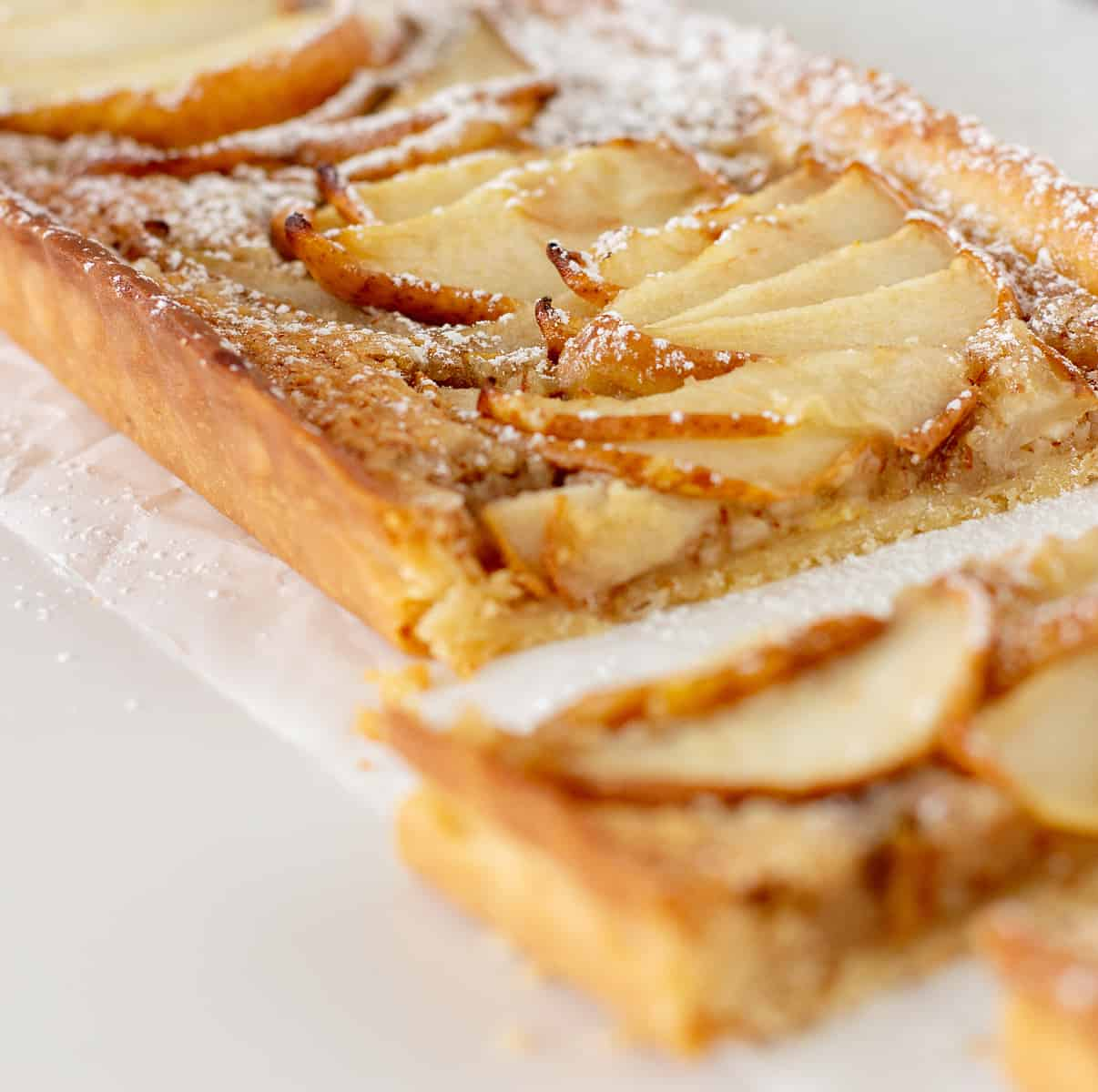 Partial view of pear frangipane tart on white surface