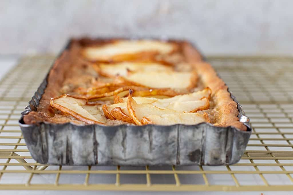 Flat view of pear tart in metal pan on wire rack