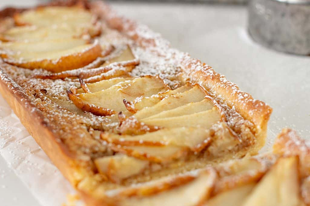Cut rectangular pear tart on white surface