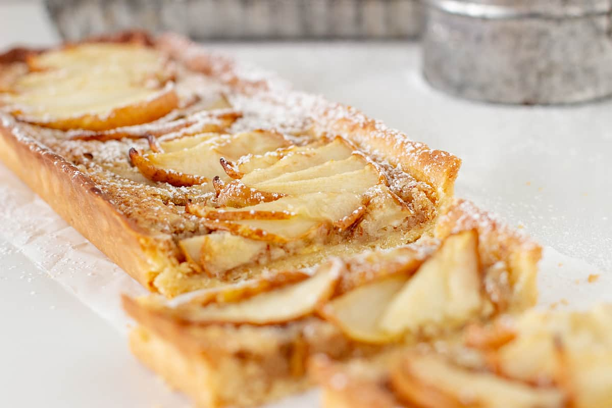 Pear Frangipane Tart on white surface, metal pans in the background
