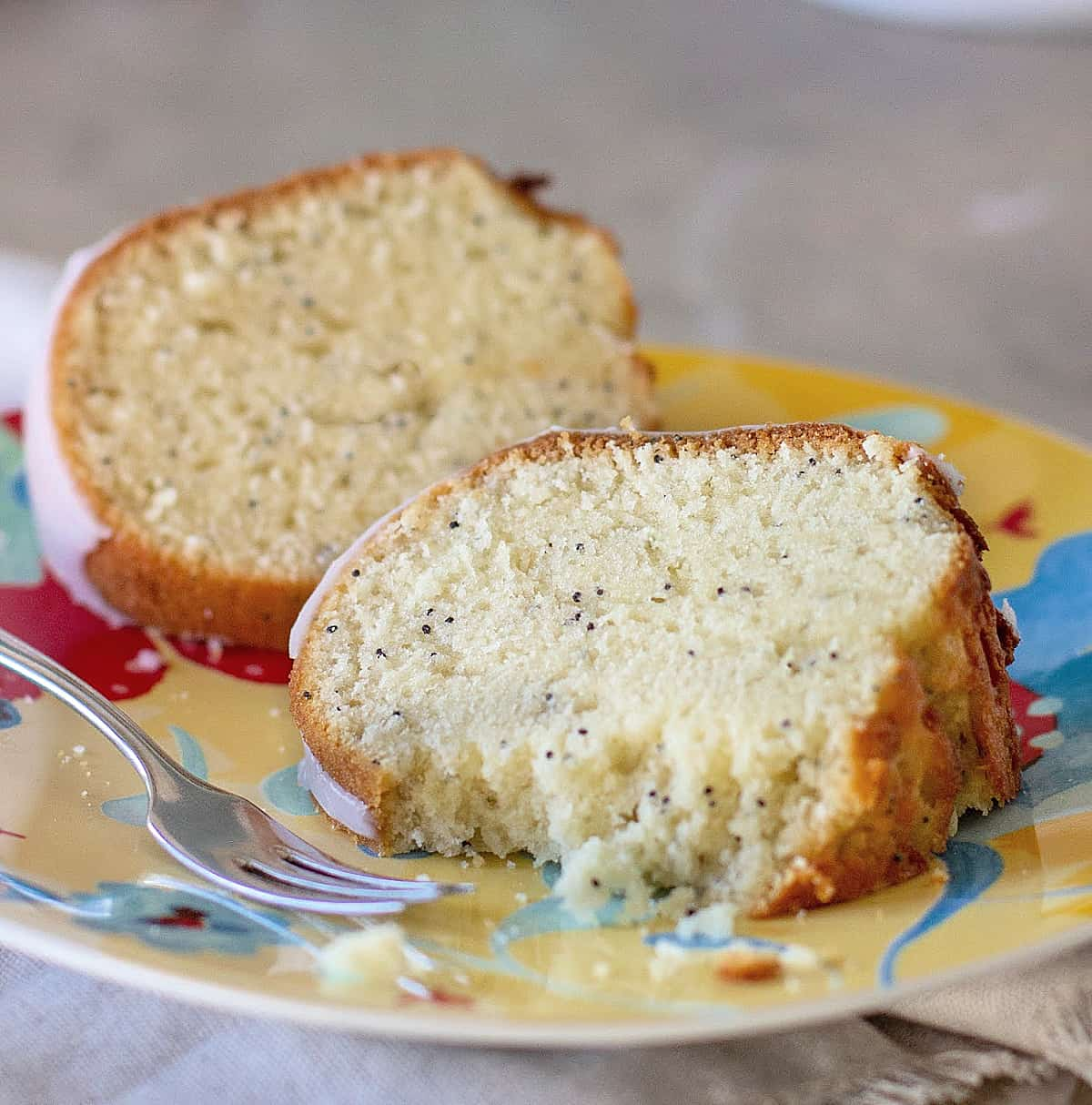Close-up of slices of poppy seed bundt cake on a colorful plate, a silver fork, grey surface
