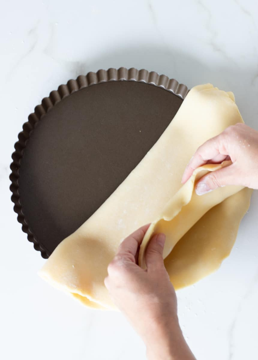 Hands lining pie pan with Unbaked sweet shortcrust pastry