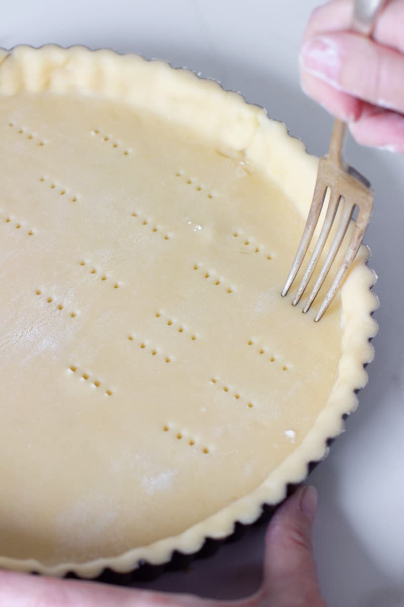 Fork pricking unbaked tart dough on white surface