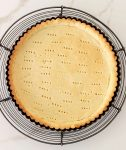 Round tart pan with baked homemade pie crust on wire rack