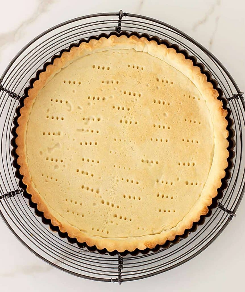 Baked shortcrust pastry on metal tart pan on wire rack