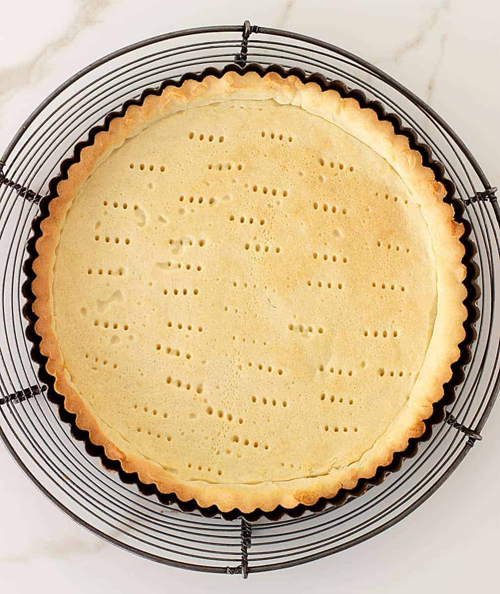 Baked shortcrust pastry on metal tart pan on wire rack, white marble surface