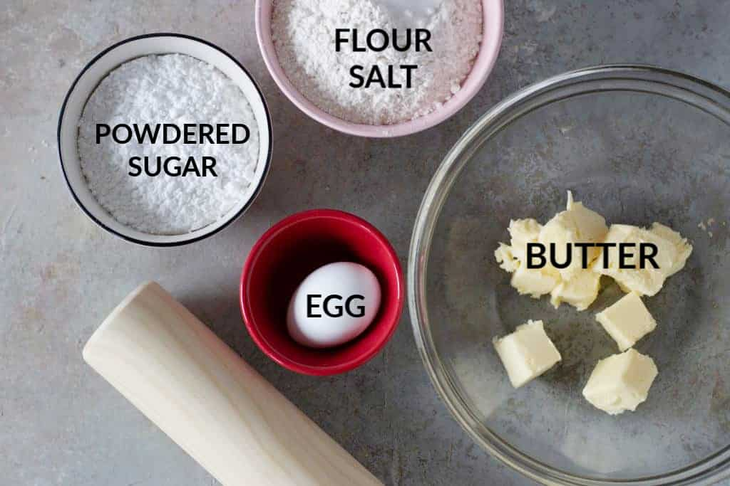 Sweet shortcrust pastry ingredients on bowls, a rolling pin, grey surface