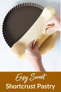 Hands lining pan with sweet shortcrust pastry
