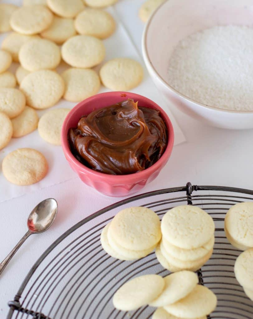Cornstarch cookies on wire rack, dulce de leche in pink bowl, coconut in bowl, white surface
