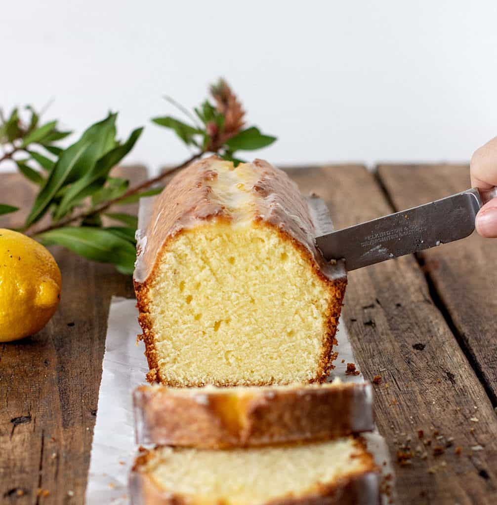 Cutting lemon pound cake  on wooden board, green leaves and a lemon in background