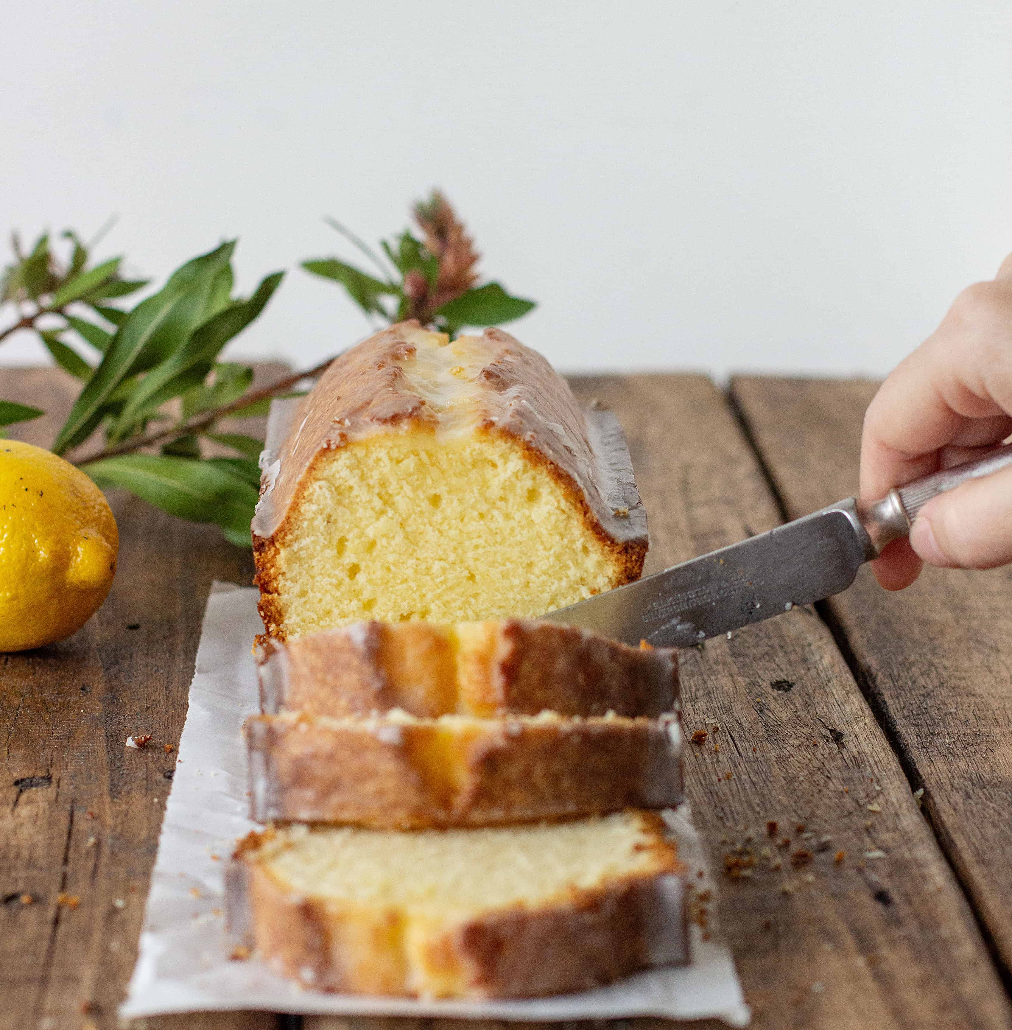 Cutting pound cake slices on a wooden board, lemon and leaves as props