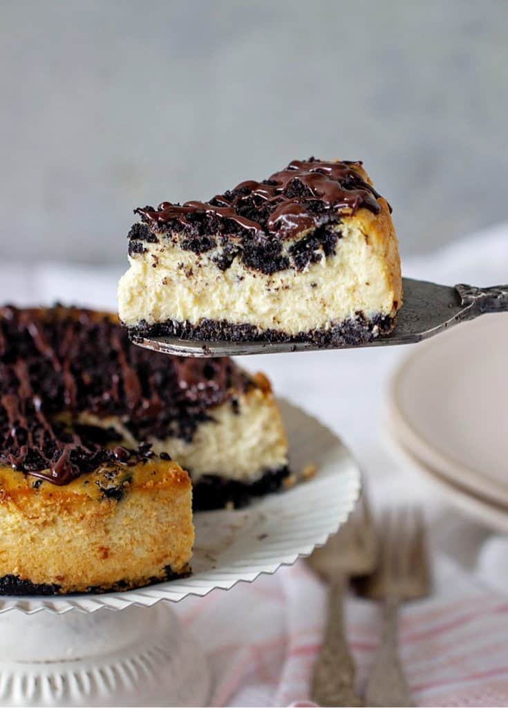 Oreo cheesecake on cake stand, slice on cake server forks, plates