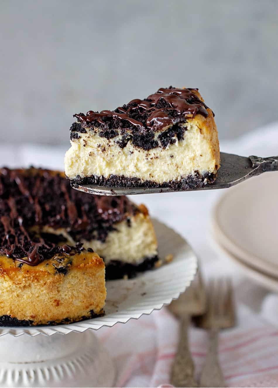 Oreo cheesecake on white cake stand, slice on cake server, forks and plates on background