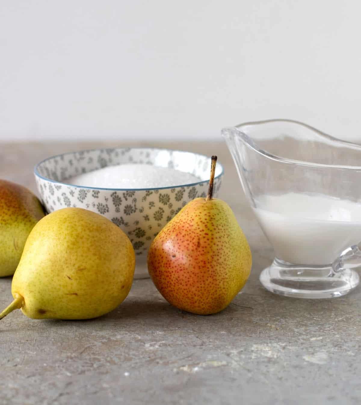 Whole pears, grey bowl with sugar, glass jar, grey background