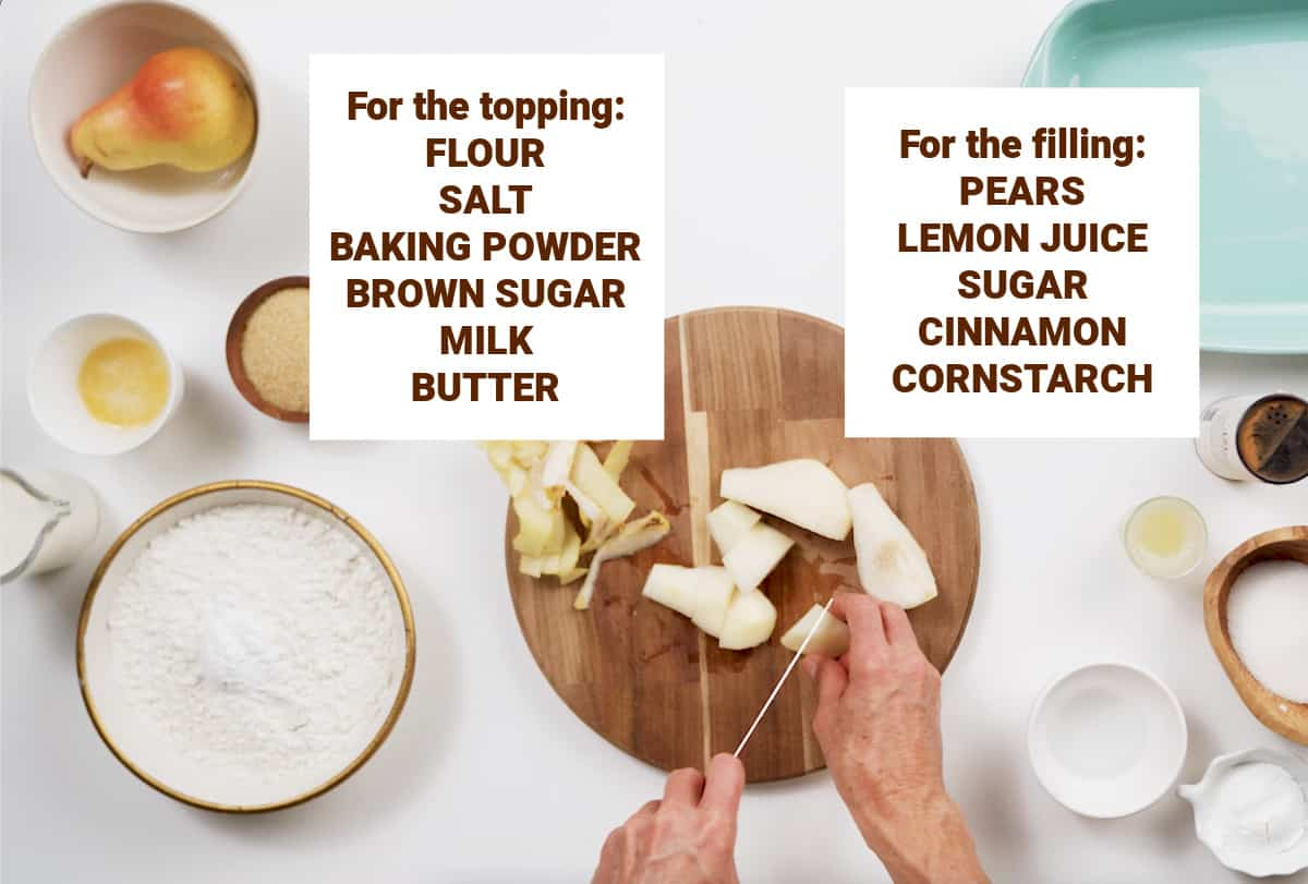 White surface with bowls containing ingredients for pear cobbler and hands cutting pears on wooden board