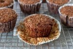 Bran muffin in paper cup on wire rack with other muffins