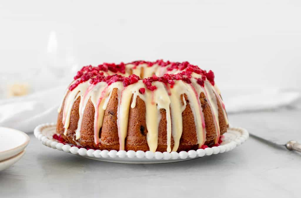 Whole white chocolate raspberry bundt cake on white plate, grey background