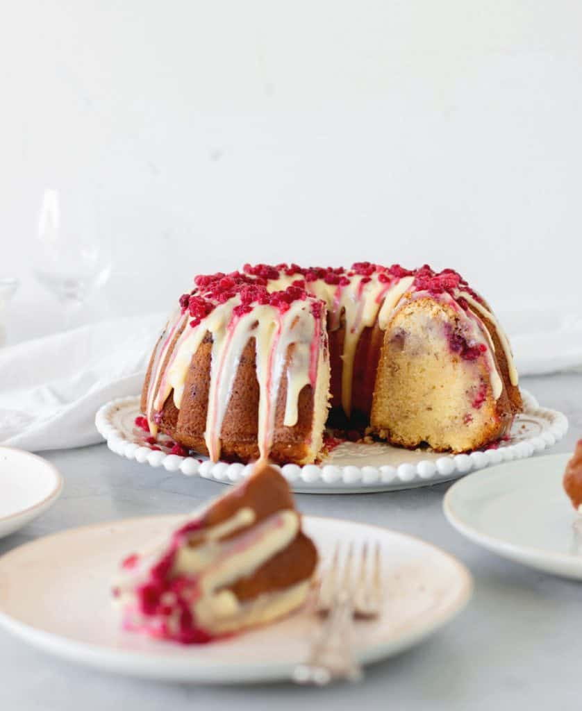 White chocolate raspberry bundt cake on white plate, slice on another plate, grey background