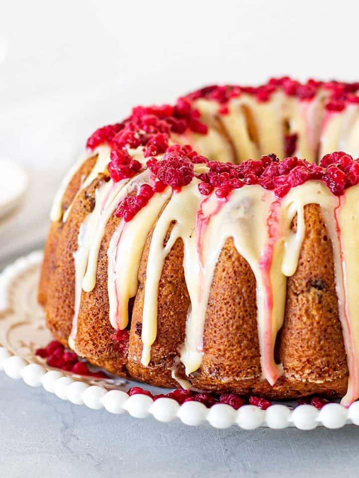 Glazed white chocolate raspberry bundt cake on white plate, grey background