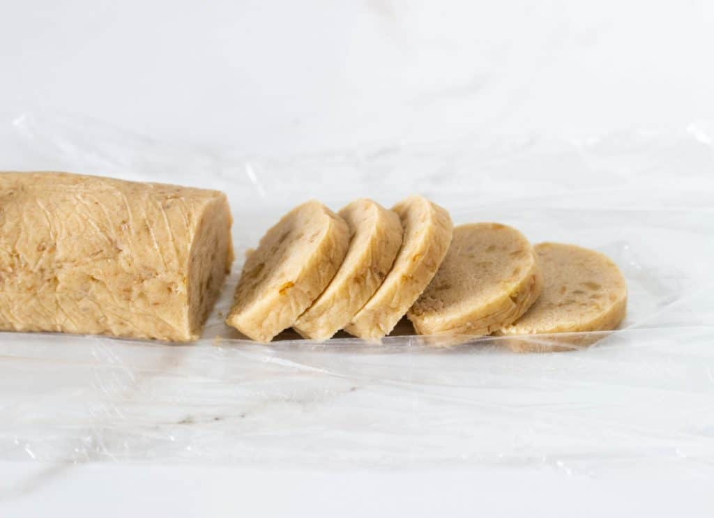 Cylinder of raw cookie dough on white surface, cut slices
