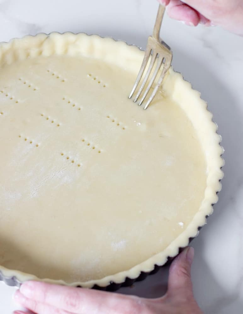 Pricking pie crust with fork, hands holding pan, white surface