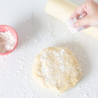 Hand flouring basic pie dough on white surface, rolling pin, pink bowl