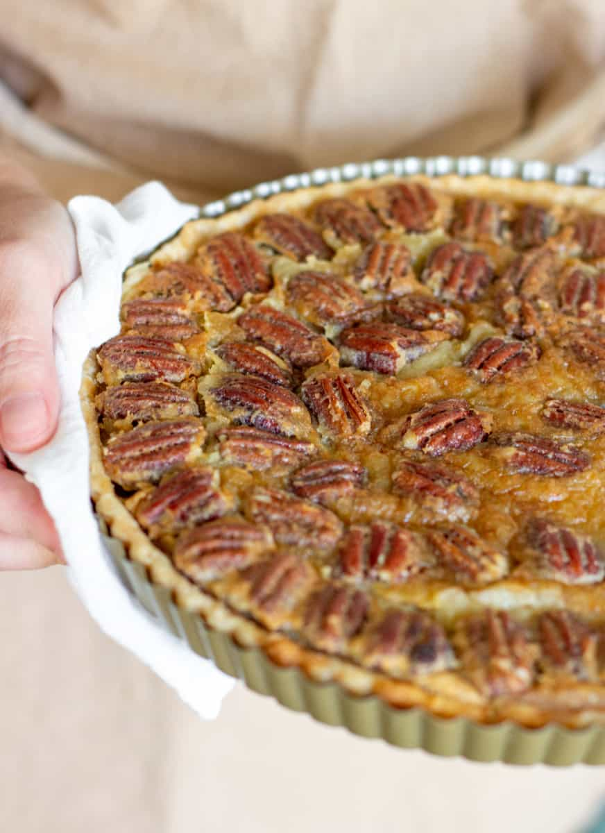 Hand holding pecan pie in pan, white kitchen towel