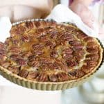 Hands holding pan with pecan pie with white kitchen towel