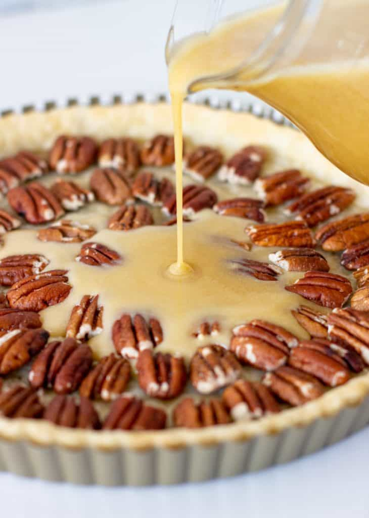 Bourbon butter filling being poured in a pie crust filled with pecans