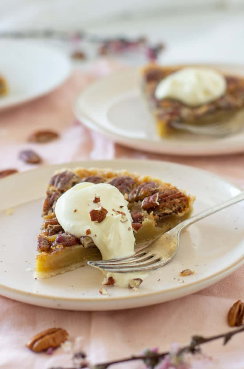 Slices of pecan pie in light pink plates, dollop of cream, fork. Pink tablecloth