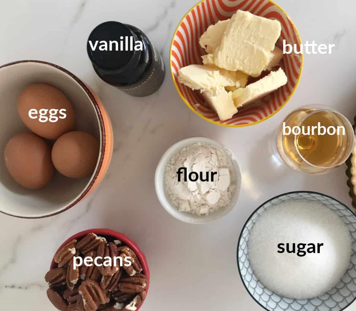 Bourbon Pecan Pie ingredients.in bowl on white surface