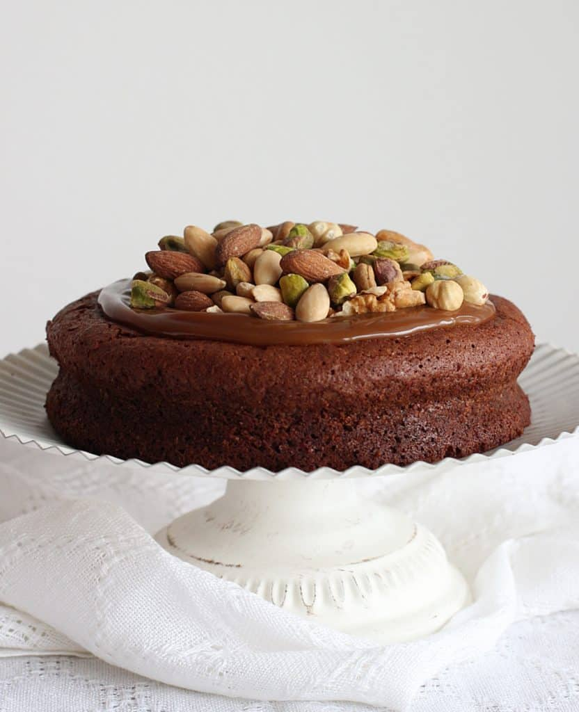 Nut topped Chocolate cake on white cake stand, white background