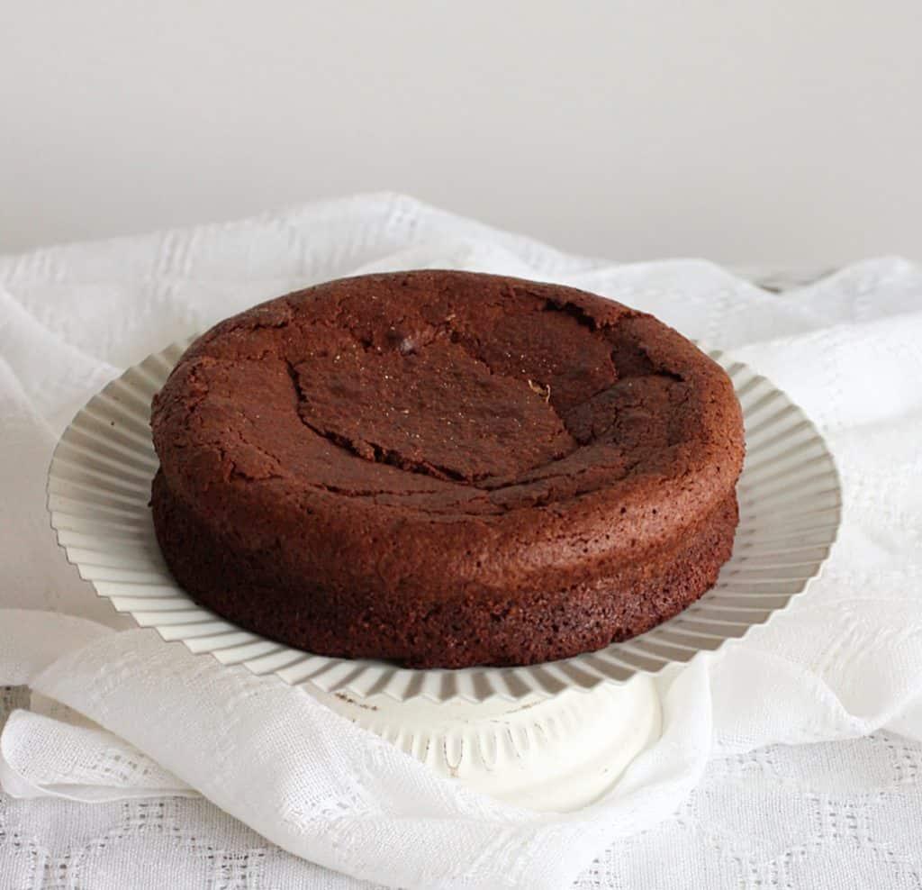 Plain Chocolate cake on white cake stand, white background