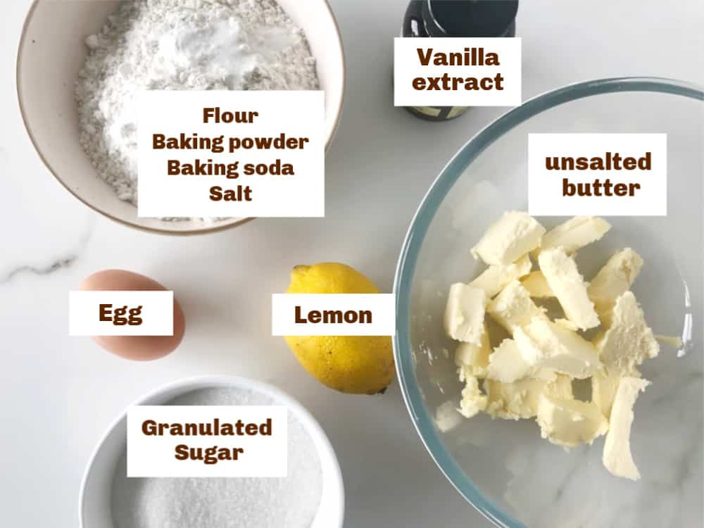 Lemon cookies ingredients.in bowls on white surface
