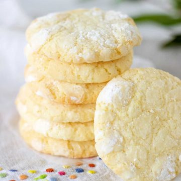 Stack of lemon crinkle cookies, white cloth with color dots, green leaves in background