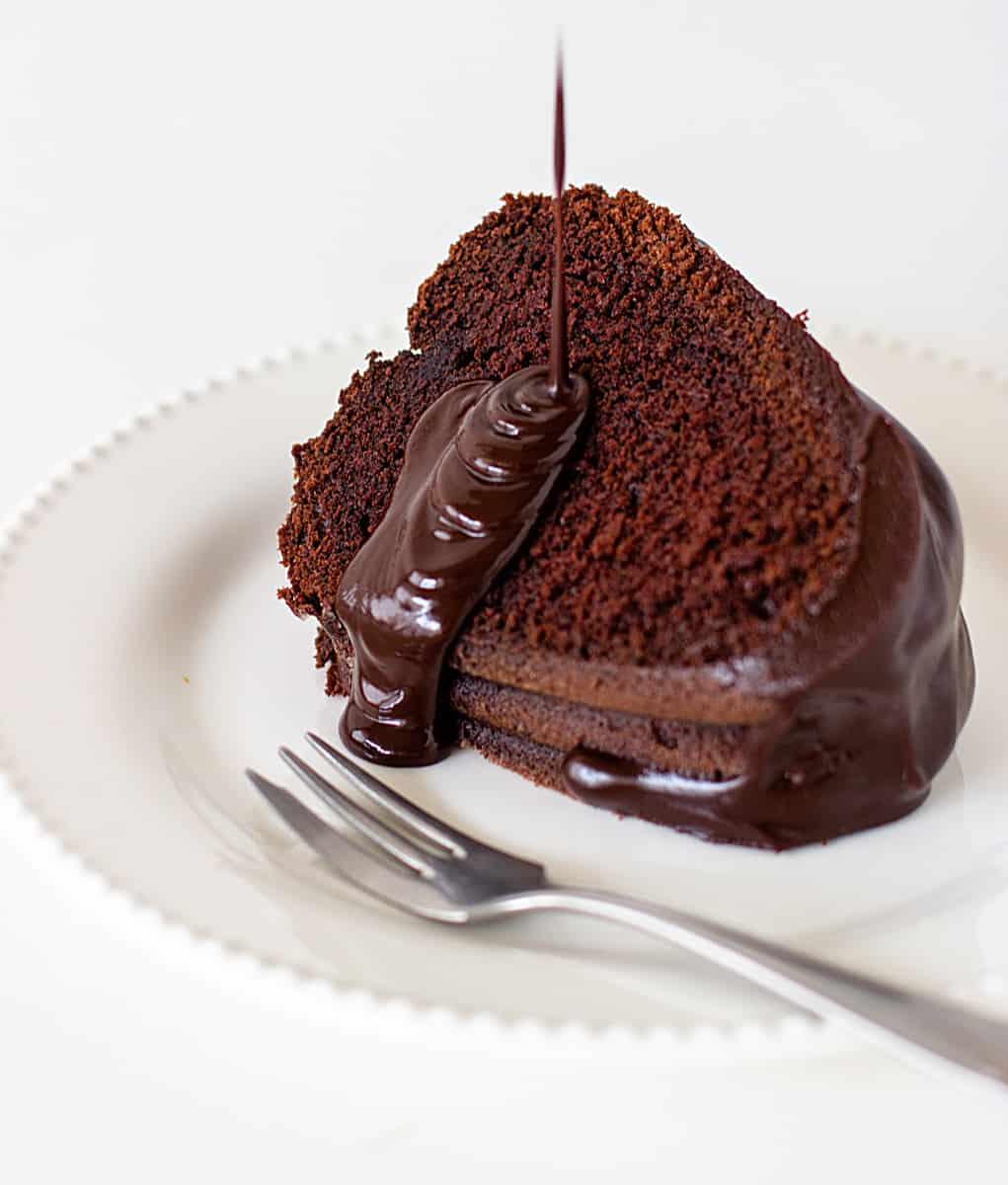Slice of chocolate bundt cake on white plate, glaze pouring